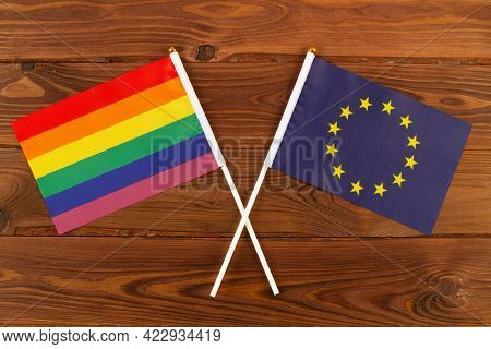 Rainbow Flag Lgbt And Flag Of European Union Eu On Brown Wood Planks Background. Lgbt Pride Month. L