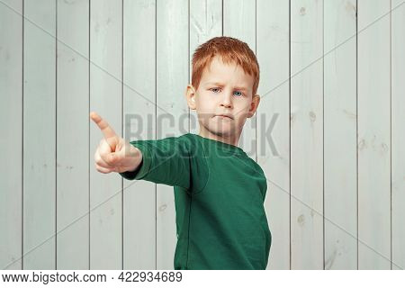 Serious Ginger Little Boy 7-9 Years Old Standing And Pointing On You Over Wooden Background
