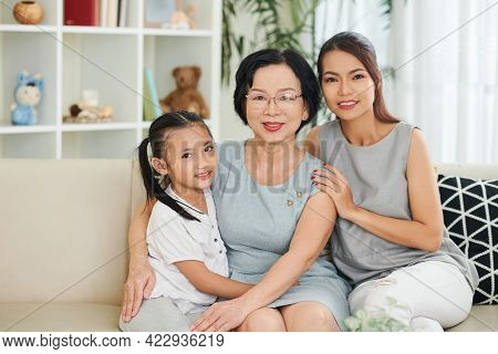 Pretty Smiling Young Woman And Preteen Daughter Visiting Her Senior Mother At Home For Holidays