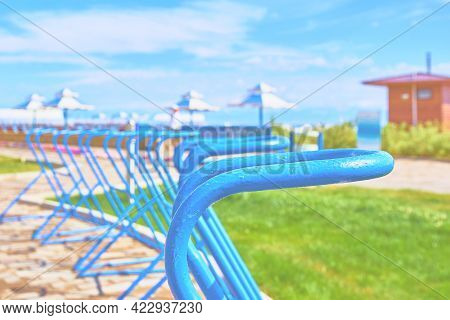 Bike Parking Places On Ocean. Sea Beach In Clear Weather. Beach Umbrellas, Sun Beds And Blue Sky In