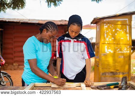Professional Female Carpenter And Her Apprentice Carefully Taking Measurement