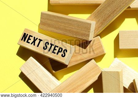 The Next Steps Text Is Written On One Of The Many Scattered Wooden Blocks, Against A Yellow Backgrou