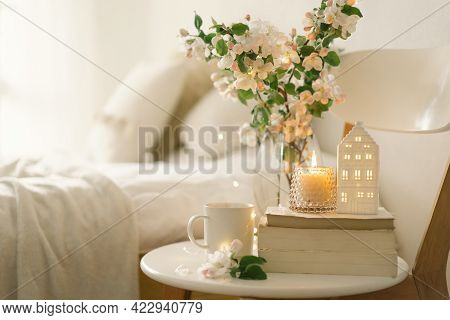 Book, Hot Cup Tea, Candle And Vase With Apple Spring Flowers.