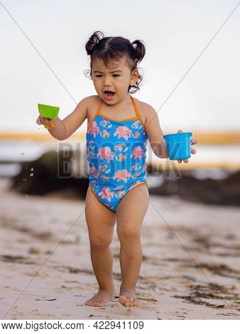 Cute Little Girl Walking On Sandy Beach, Playing With Sand Scoop And Bucket. Happy Childhood. Summer