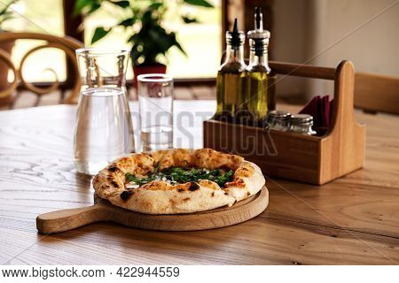 Pizza And Water In Glass Jug On Wooden Table In Vintage Style. Italian Restaurant Background For You