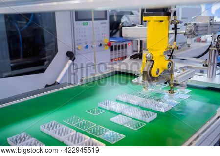Pick And Place Yellow Robotic Arm Manipulator Moving Flat Plastic Details On Conveyor Belt At Modern