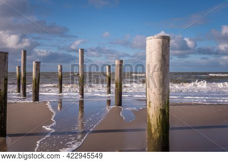 Petten, The Netherlands. March 3, 2021. Wooden Poles At The Beach Near Petten Aan Zee, The Netherlan