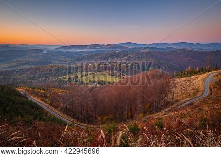 Rural Landscape With Dirt Road. Hills And Forests In Autumn Colors At Sunset.