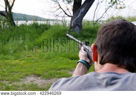 A Young Guy Is Preparing To Shoot From A Pneumatic Weapon. Aims At A Jar Hanging From A Tree.