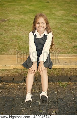 Cause Your Little One Deserves It. Happy Child Sit On Bench Outdoors. School Look Of Child Girl. For