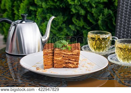 Medovik Cake Covered With Crumbs, Two Cups With Mint Tea And Steel Kettle On Table In Summer Cafe. T