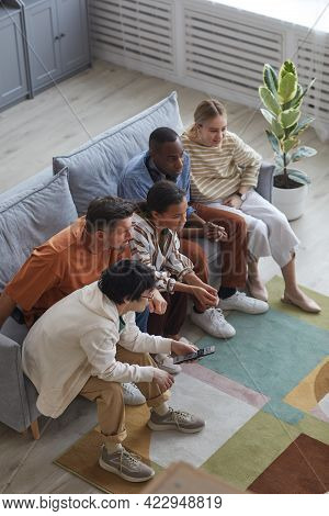 Vertical High Angle View At Multi-ethnic Group Of Friends Watching Tv At Home Together While Sitting