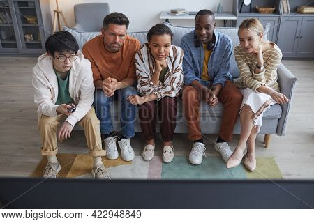 Full Length Portrait Multi-ethnic Group Of Friends Watching Tv At Home Together While Sitting In Row