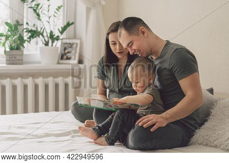 Family Love. Parents And Little Son Reading Book Together