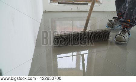 Leveling The Floor Using Spiked Roller In Empty Room. Roll Out The Self-leveling Floor Using A Needl