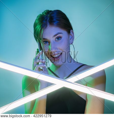 Phone Call. Mobile Communication. Futuristic Technology. Green Blue Neon Light Surprised Curious Wom