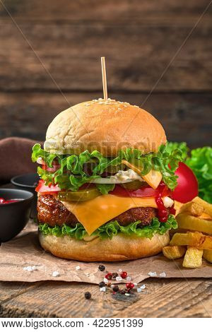 Burger With Beef Patty, Vegetables And Cheese And French Fries On A Brown Background.