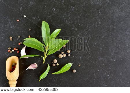 Fresh Bay Leaf, Allspice And Pepper Mix On Dark Stone Background With Copy Space. Top View, Flat Lay