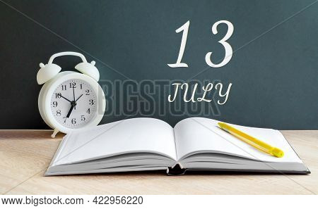 July 13. 13-th Day Of The Month, Calendar Date.a White Alarm Clock, An Open Notebook With Blank Page