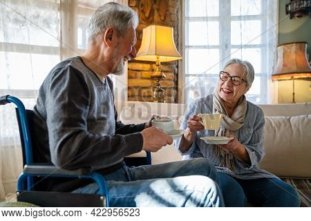Mature Man With Disability In Wheelchair. Happy Retired Senior Couple Having Fun At Home.