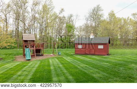 An Outdoor Shed And Childs Playset On A Freshly Mown Lawn.