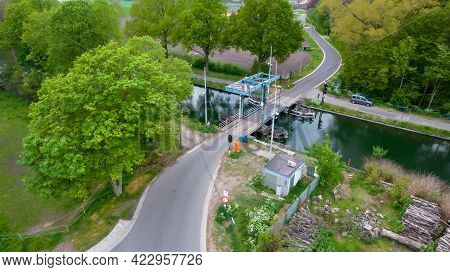 Aerial Shot Of A Drawbridge Over A Canal Or River In A Green Countryside Landscape In Flanders, Belg