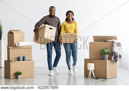 Relocation Concept. Portrait Of Cheerful Black Spouses Moving To New Apartment