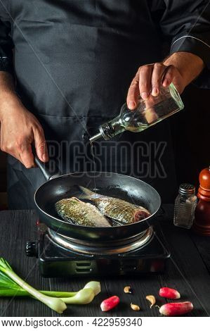 The Chef Prepares Fresh Fish In A Pan With Oil. Preparation For Cooking Fish Food. Working Environme