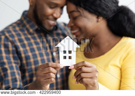 African American Spouses Holding Cutout Paper House Figure In Hands