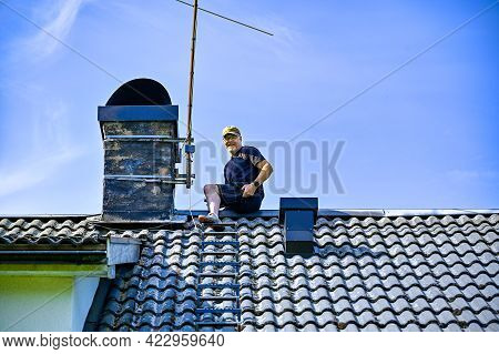 A Man Taking Down An Old Tv-antenna