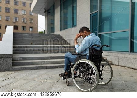 Upset Handicapped Black Man In Wheelchair In Front Of Stairs Without Ramp, Having No Possibility To