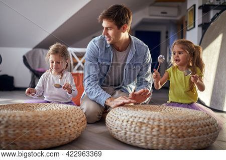 Little daughters with spoons sitting on the floor in a cheerful atmosphere at home and enjoy drumming with their father. Family, together, playtime, home