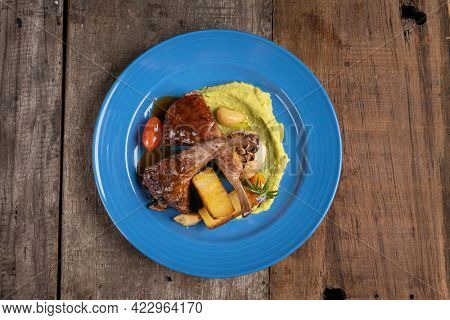 Top view of two grilled lamb chops and potatoes served on pea puree with a mint sauce isolated on rustic wooden table