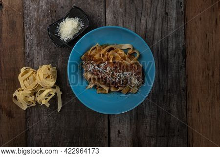 Top view of spicy pasta Bolognese with fettuccini pasta isolated on the wooden table
