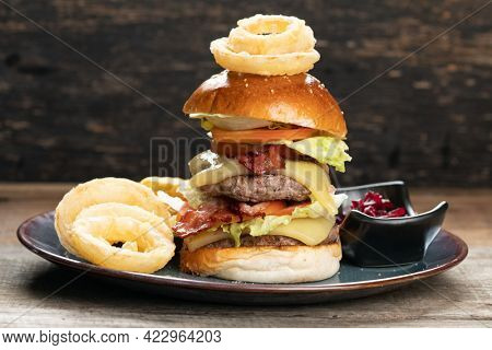 Big burger with beef, bacon, tomato, cheese, lettuce and onion served with french fries, onion rings and beetroot salad on the side isolated on rustic wooden table