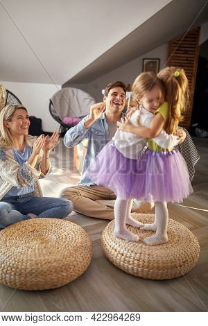 Little sisters are hugging while having a good time with their parents in a cheerful atmosphere at home. Family, together, playtime, home