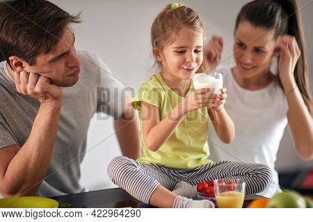 A young happy parents watching their daughter enjoying a yogurt for a breakfast in a cheerful atmosphere at home. Family, breakfast, playing, togetherness