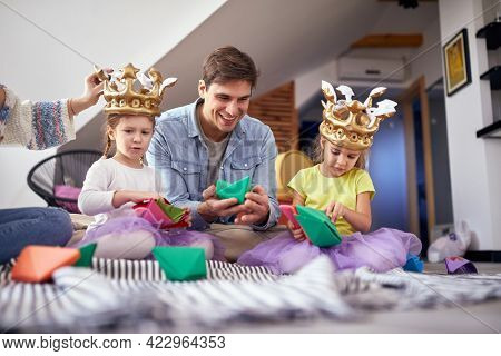 A young family sitting on the floor in a cheerful atmosphere at home and playing with paper boats. Family, together, playtime, home