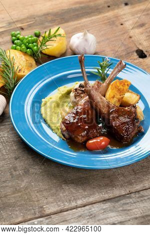 Two grilled lamb chops and potatoes served on pea puree with a mint sauce isolated on rustic wooden table