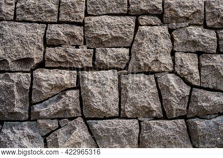 Closeup Front View Of A Massive Stone Wall With Sharp Lines Outdoors.