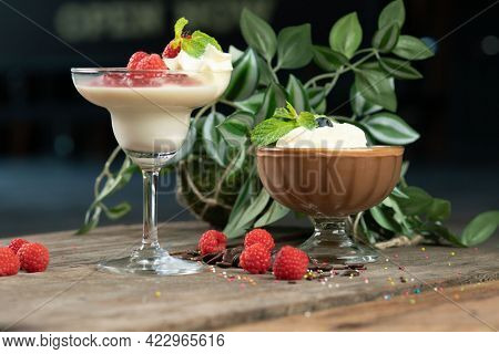 Raspberry Panna Cotta and chocolate mousse isolated on the wooden table