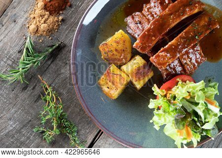 Slow baked pork cooked in brown sugar, cumin, smoked paprika and garlic powder in bbq sauce served with potatoes and salad isolated on the wooden table