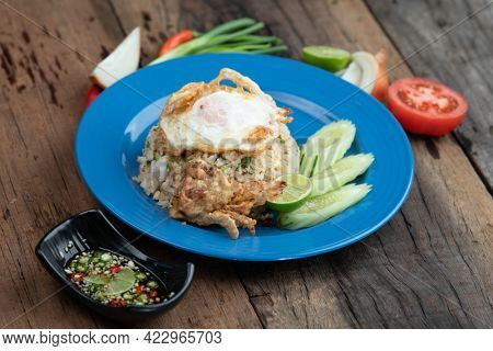 Fried rice with egg on top, pork crackling and cucumber isolated on rustic wooden table