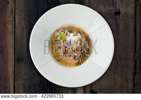 Prawns, white snapper, squid, salmon in a spicy orange dressing isolated on the wooden table