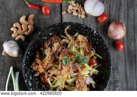 Somtam (Papaya Salad) with pork crackling isolated on rustic wooden table