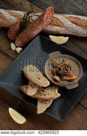 Gambas Pil Pil - Sizzling prawns with chili and garlic served with bread on the side isolated on wooden rustic table