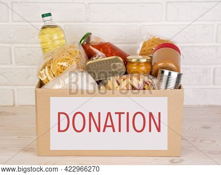 Food donations such as pasta, rice, oil, peanut butter, canned food, jam and other in a cardboard box on a brown table