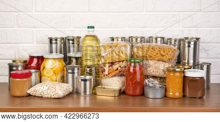 Food donations such as pasta, rice, oil, peanut butter, canned food, jam and other on brown table