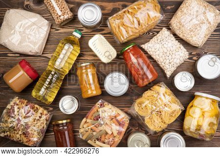 Food donations such as pasta, rice, oil, peanut butter, canned food, jam and other on brown wooden table , top view