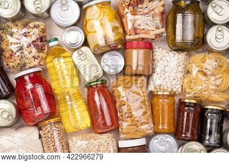 Food donations such as pasta, rice, oil, peanut butter, canned food, jam and other on white wooden table , top view